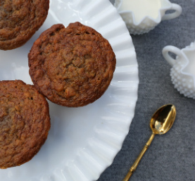 Ginger carrot muffins on a white plate, gold spoon, sugar bowl, milk jug on a grey table cloth