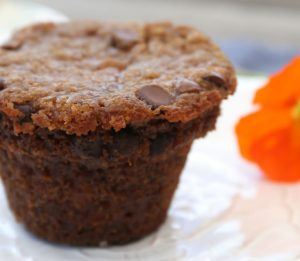 Close up of a banana chocolate chip muffin on a white plate with an orange poppy in the background right side