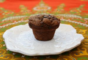 One chocolate chip muffin on a white, round plate sitting on a table cloth with a red, green and yellow design