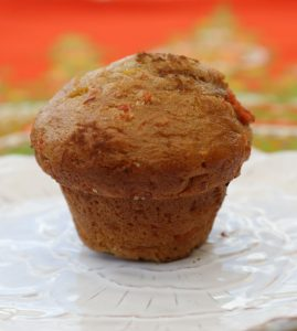 A ginger carrot muffin on a white plate with an out of focus orange and green tablecloth in the background