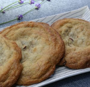 Chocolate chip cookies on a white ceramic tray on a grey table cloth with some sprigs of lavender in the background