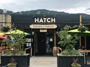 Exterior image of Hatch Restaurant, Jackson Hole, WY front patio with green umbrellas and potted plants