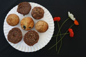 7 muffins viewed from above on a white plate, white and red poppies to the right of the plate all on a black background