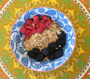 View from above of a blue and white bowl full of granola, blackberries and raspberries on a table cloth with a yellow and green design