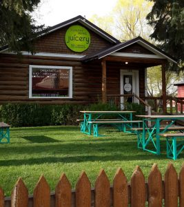 Exterior shot of Healthy Being Cafe, Jackson, WY with picnic tables and green lawn