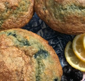 3 partial Blueberry lemon muffins on dark blue plate with lemons slices and 3 loose blueberries l